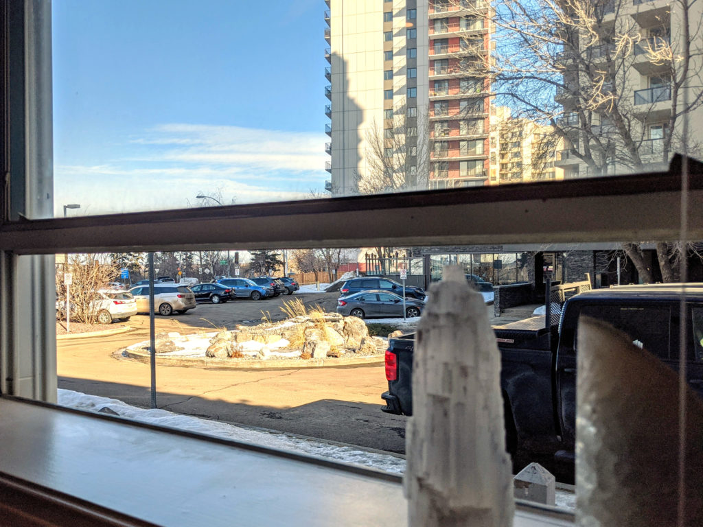 Micromeditating as self-care. A picture of a parking lot and buildings taken from a window.