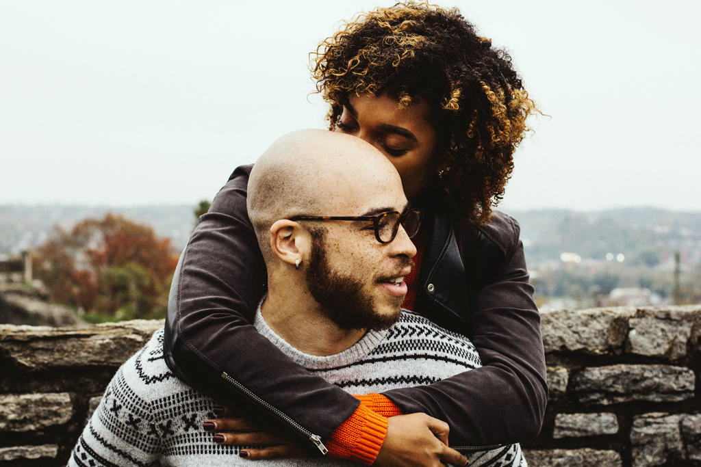 Authenticity and attachment, A photograph of a woman hugging a man from behind and kissing his head; they are outdoors.