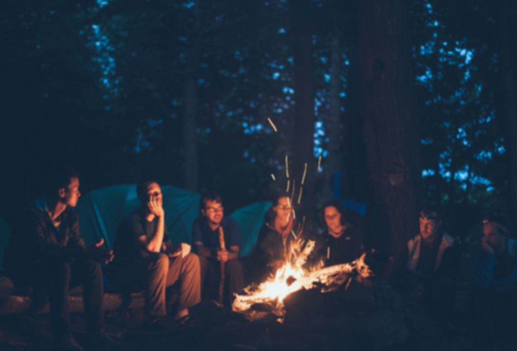 A group of people sitting by a campfire at night, listening to each other.