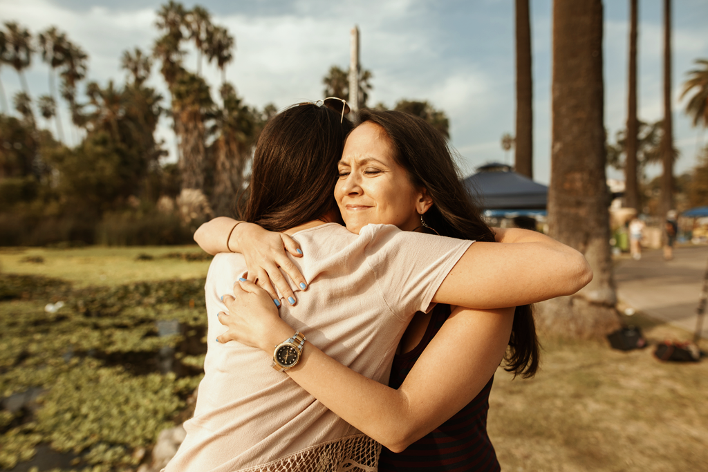 Suicide Prevention Awareness Day. A photo of two women hugging each other. They are standing outdoors in a park, you can see a lake and trees behind them.