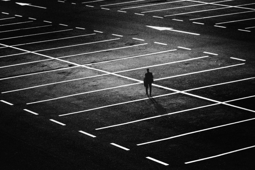 The traumatizing experience of systemic discrimination. A black and white picture of a person walking alone in an empty parking lot.