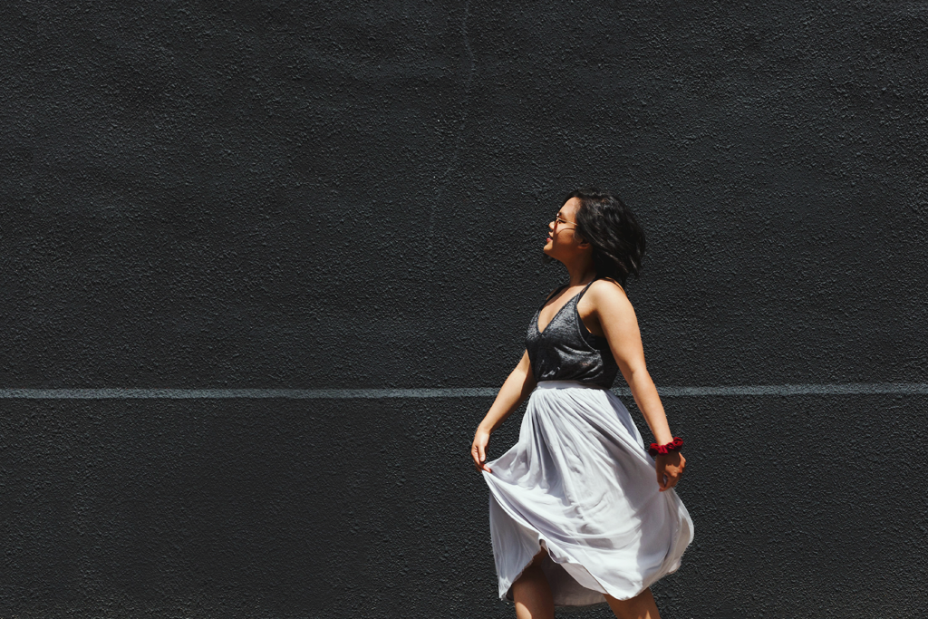 A woman walking along a grey wall background, looking content. It symbolizes a self-care practice.