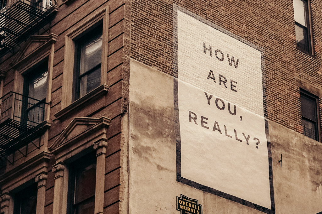 "Understanding our emotions. A picture of the side of a building, showing a painted mural that says ""How are you, really?"""